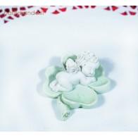 Maža angelo statula žalioje gėlėje
